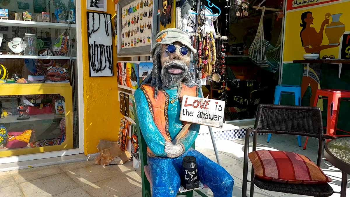 Statue of a hippie holding a sign with - Love is The Answer