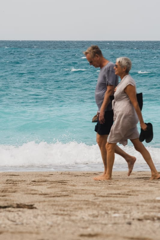 mature people walking on the beach