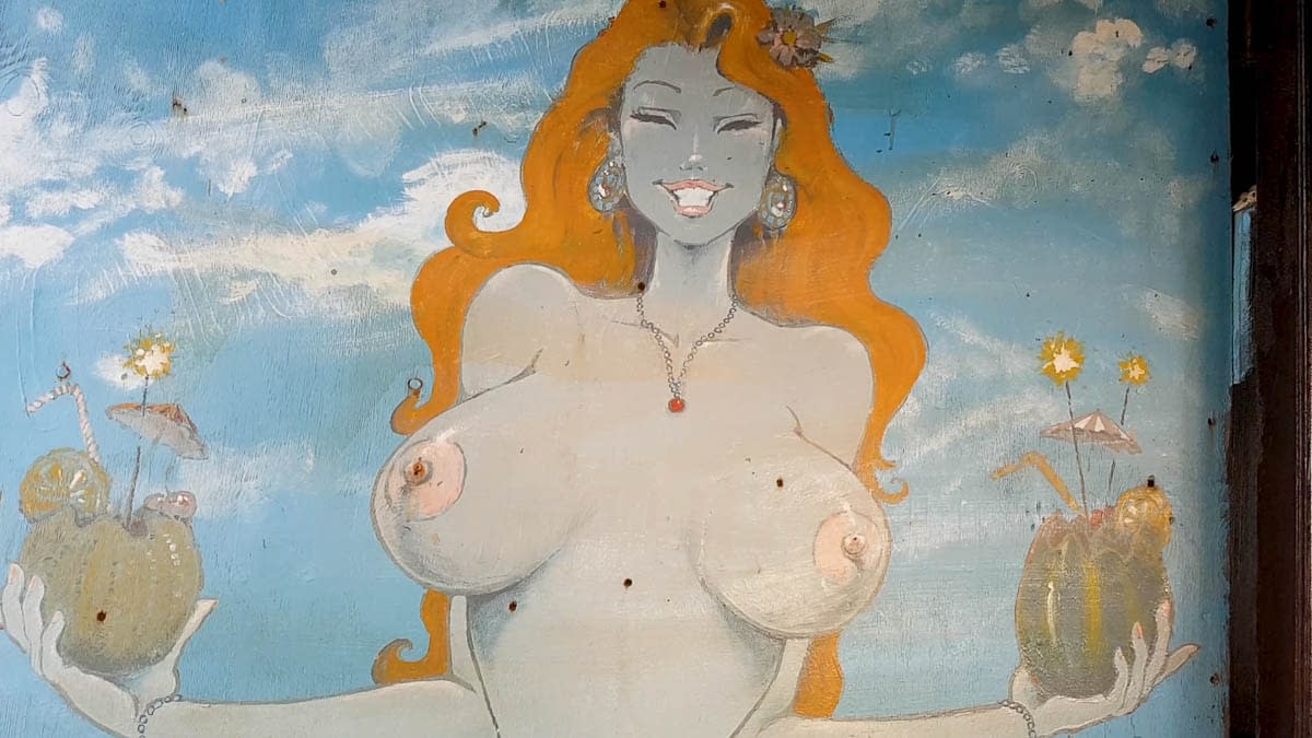 Wall painting in Matala showing a topless lady serving coktails